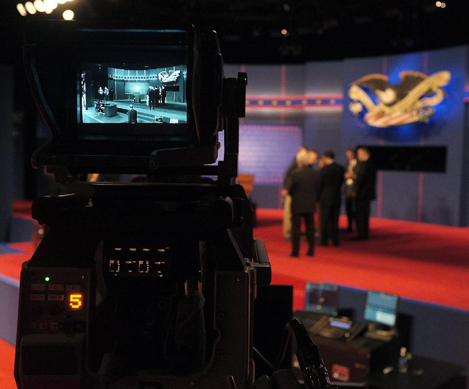 Last minute stage setup for the first Presidential Debate between President Barack Obama and Republican presidential nominee Mitt Romney at the University of Denver take place as seen in a television camera monitor Wednesday, Oct. 3, 2012, in Denver. (AP Photo/J. David Ake)