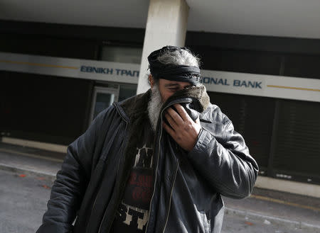 Greek farmer covers his face to avoid breathing tear gas during clashes with police at a protest against planned pension reforms outside the Agriculture ministry in Athens