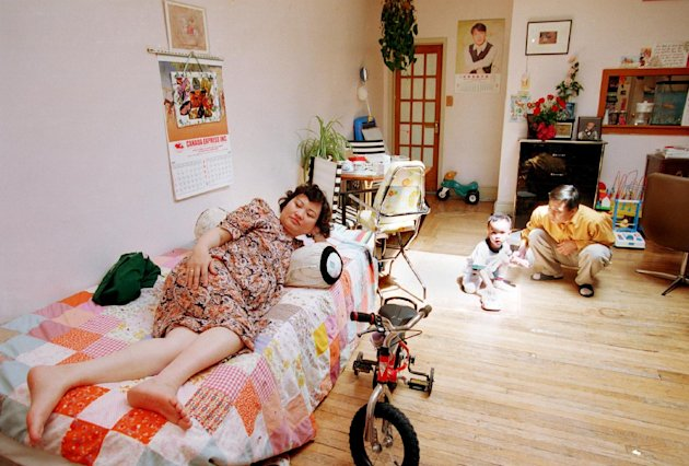 FILE - In this June 8, 1992 file photo, Phan Thi Kim Phuc, left, watches television as her husband, Bui Huy Toan, plays with their son Thomas, 3, in their apartment in Toronto. Phuc, who was the main