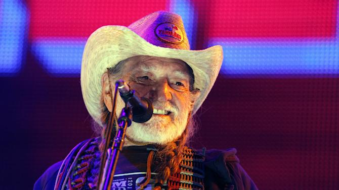 """FILE - This Sept. 22, 2012, file photo shows country music legend Willie Nelson performing during the Farm Aid 2012 concert at Hersheypark Stadium in Hershey, Pa. Nelson will release """"Roll Me Up And Smoke Me When I Die"""" on Nov. 13. Publisher William Morrow says the American music icon will tell never-before-heard stories about his life, family, music, politics, Texas, religion and favorite recreational activity. (AP Photo/Jacqueline Larma, File)"""