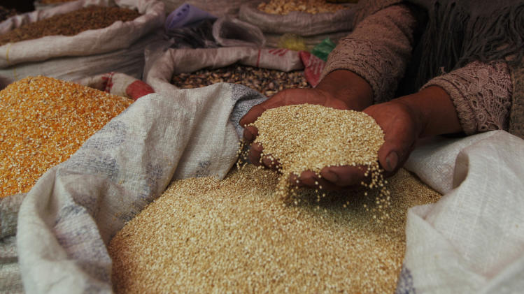 "A woman shows her quinoa grain for sale at a market in La Paz, Bolivia, Friday March 2, 2012.  Bolivian authorities say at least 30 people have been injured in a fight between two communities over land for growing quinoa, the Andean ""super-grain"" whose popularity with worldwide foodies has caused its price to soar. Bolivia produces 46 percent of the world's quinoa, which has nearly tripled in price in the past five years. (AP Photo/Juan Karita)"