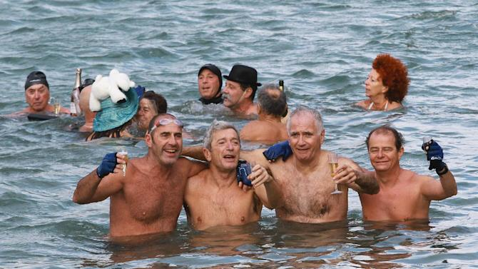 Enthusiasts from the long-established swimming club, Les Ours Blancs (The Polar Bears), drink champagne during an annual New Year's celebration swimming in Biarritz, southwestern France, Tuesday, Jan. 1, 2013.(AP Photo/Bob Edme)