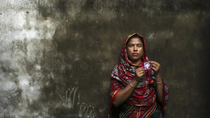 In this Friday, Dec. 21, 2012 photo, Bangladeshi Rumana Begum, 33, holds a photograph of her 18-year-old daughter Mukhtar Begum,a senior sewing machine operator who died in the fire at Tazreen Fashions, in the garment district in Ashulia, near Dhaka, Bangladesh. When fire ravaged the Bangladeshi garment factory, killing 112 workers, dozens of their families did not even have a body to bury because their loved ones' remains were burned beyond recognition. Two months later, they have yet to receive any of the compensation they were promised - not even their relatives' last paychecks.  (AP Photo/Kevin Frayer)