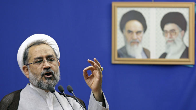 Iranian Intelligence Minister Heidar Moslehi delivers a speech in front of portraits of the late Ayatollah Khomeini, left, and supreme leader Ayatollah Ali Khamenei, during Friday prayers at Tehran University in Tehran, Iran, Friday, July 6, 2012. Moslehi accused French and German intelligence services of cooperating with the CIA to kill Iranian nuclear scientists. (AP Photo/Vahid Salemi)