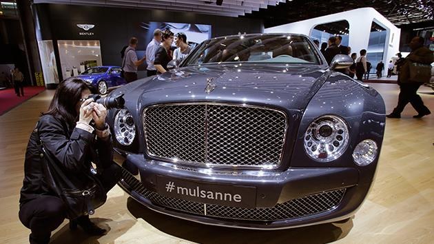 A woman takes pictures of a Bentley Mulsanne, during the press day on the eve of the opening of the Paris Auto Show.