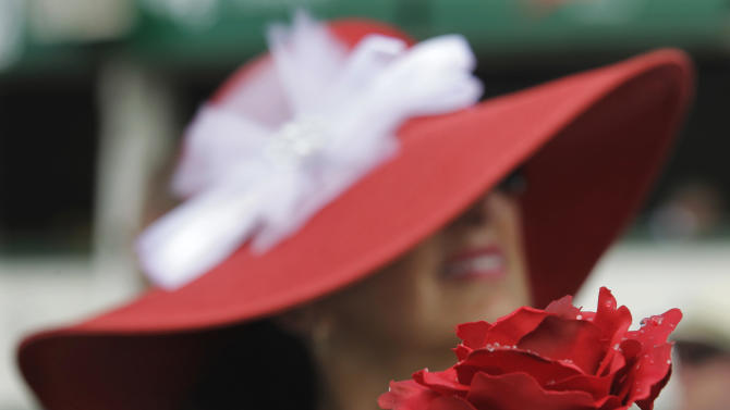 Mary Bowe, from Maples, Fla., holds a rose while sitting in the grandstand before the 138th Kentucky Derby horse race at Churchill Downs, Saturday, May 5, 2012, in Louisville, Ky. The Run for the Roses draws them to Churchill Downs. But what race goers wear is as much a spectacle in itself. (AP Photo/Michael Conroy)