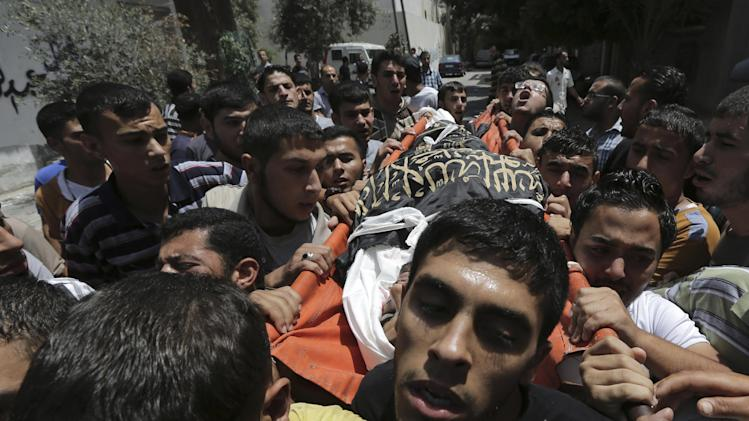Palestinians carry the body of Islamic Jihad militant Mohammed Sowelim, who was killed in an Israeli air strike, during his funeral in Jabaliya refugee camp, in the northern Gaza Strip, Saturday, July 12, 2014. Israeli airstrikes targeting Hamas in Gaza hit a mosque and a center for the disabled where two women were killed Saturday, raising the Palestinian death toll from the offensive to more than 120, Palestinian officials said. (AP Photo/Adel Hana)