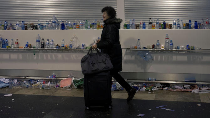 A passenger walks past accumulated garbage during a cleaners strike, at Barajas international airport in Madrid, Monday Jan. 28, 2013. Battling to reduce a swollen deficit and avoid a bailout, the year-old conservative government has brought major financial and labor reforms and applied severe cutbacks in wages and spending but so far the economy has shown few signs of recovery. (AP Photo/Paul White)