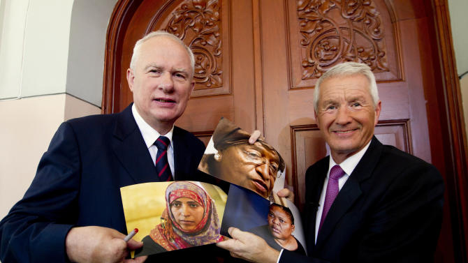Norwegian Nobel Committee chairman Thorbjoern Jagland, right, and Permanent Secretary Geir Lundestad, left, hold up photographs of Liberian President Ellen Johnson Sirleaf, center top, Liberian peace activist Leymah Gbowee, center right, and Tawakkul Karman of Yemen, center left, after announcing them as the recipients of the 2011 Nobel Peace prize in Oslo, Norway, Friday, Oct. 7, 2011. The 2011 Nobel Peace Prize was awarded Friday to Liberian President Ellen Johnson Sirleaf, Liberian peace activist Leymah Gbowee and Tawakkul Karman of Yemen for their work on women's rights. (AP Photo/Scanpix Norway, Terje Bendiksby) NORWAY OUT