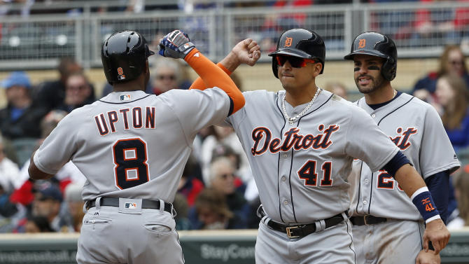 Detroit Tigers' Victor Martinez (41) and J.D. Martinez, right, welcome home Justin Upton (8) after Upton's three-run home run off Minnesota Twins starting pitcher Tyler Duffey during the first inning of a baseball game in Minneapolis, Saturday, April 30, 2016. (AP Photo/Ann Heisenfelt)