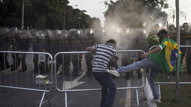 A protester kicks another one as he tried to prevent him from breaking a police barrier during a protest outside Minerao stadium where a Confederations Cup soccer match takes place between Japan and Mexico in Belo Horizonte, Brazil, Saturday, June 22, 2013. Demonstrators once again took to the streets of Brazil on Saturday, continuing a wave of protests that have shaken the nation and pushed the government to promise a crackdown on corruption and greater spending on social services. (AP Photo/Felipe Dana)