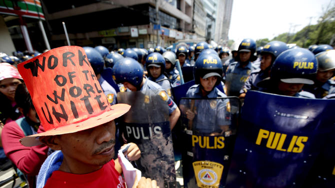 "Riot police block protesters as they try to march towards U.S. Embassy in Manila to mark International Labor Day Wednesday May 1, 2013 in Manila, Philippines. The workers, who have demanding wage increases for years, assailed President Aquino III for his Labor Day ""gift"" of non-wage benefits.  The protesters have been clamoring for years for a P125-Peso ($3.125) across-the-board wage hike and condemn the Government's policy of outsourcing labor which allegedly eliminates job security. (AP Photo/Bullit Marquez)"