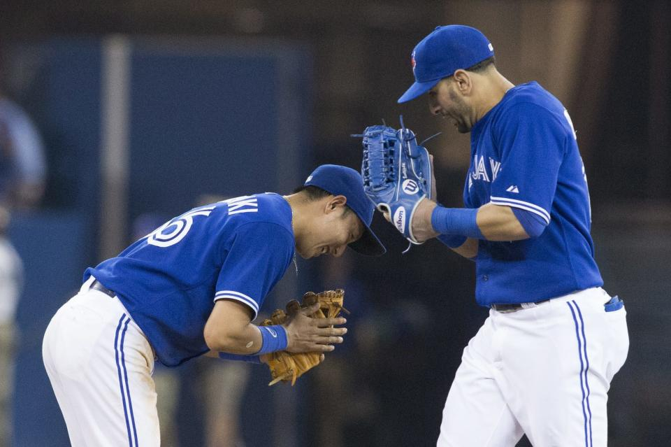 Toronto Blue Jays Munenori Kawasaki, left, bows to Jose Bautista as they celebrate their 4-2 win over the Baltimore Orioles in a baseball action in Toronto, Saturday June 22, 2013. (AP Photo/the Canadian Press, Chris Young)