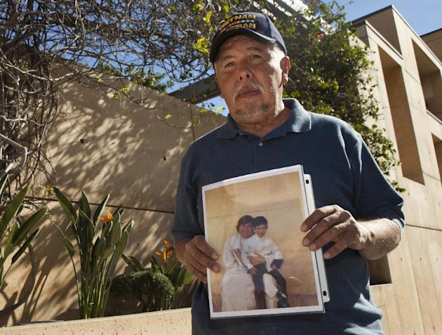 Frank Zamora, 67, holds an old photo of his son Dominic Zamora, then 8, sitting on the lap of his abuser, priest Michael Stephen Baker, as Zamora joins members the Survivors Network of those Abused by