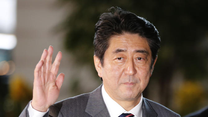 Japan's newly-named Prime Minsiter Shinzo Abe waves for the media upon his arrival at the prime minister's official residence following his election at Parliament in Tokyo Wednesday, Dec. 26, 2012. Abe, whose nationalist positions have in the past angered Japan's neighbors, is the country's seventh prime minister in just over six years. (AP Photo/Shizuo Kambayashi)