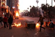 Egyptian anti-government protesters take cover behind burning bins during clashes with riot police, in the northern coastal city of Alexandria, on February 8, 2013. More than 120 people were injured in unrest across Egypt on Friday