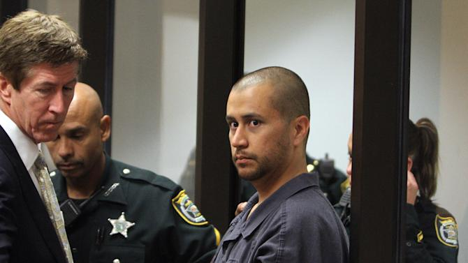 George Zimmerman, center, is directed by a Seminole County Deputy and his attorney Mark O'Mara during a court hearing Thursday April 12, 2012, in Sanford, Fla.  Zimmerman has been charged with second-degree murder in the shooting death of the 17-year-old Trayvon Martin. (AP Photo/Gary W. Green, Orlando Sentinel, Pool)