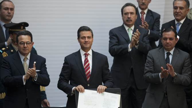"""Flanked by Mexican Senate Deputy Chairman Francisco Arroyo Vieira, left, and Mexican Senate President Ernesto Cordero, right, Mexico's President Enrique Pena Nieto, center, shows off the signed document enacting education reform, at the National Palace in Mexico City, Monday, Feb. 25, 2013. The law which was approved by Congress in December, calls for creation of a professional system for hiring, evaluating and promoting teachers without the """"discretionary criteria"""" currently used in a system where teaching positions are often bought or inherited. (AP Photo/Alexandre Meneghini)"""