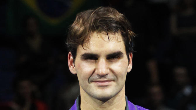 Runner-up Roger Federer of Switzerland holds his silver plate as he poses for the photographers after he was defeated by Novak Djokovic of Serbia in their ATP World Tour Tennis singles final match in London, Monday, Nov. 12, 2012. (AP Photo/Sang Tan)