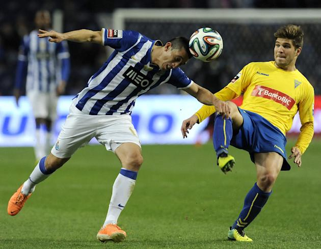FC Porto's Hector Herrera, from Mexico, heads the ball past Estoril's Diogo Amado, right, in a Portuguese League soccer match at the Dragao stadium, in Porto, Portugal, Sunday, Feb. 23, 2014.