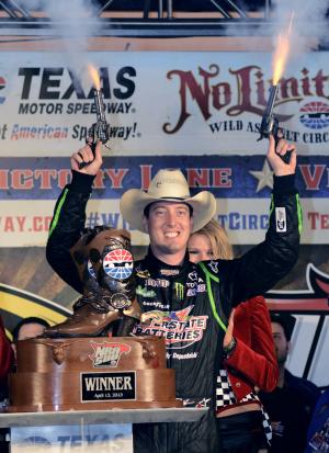 Sprint Cup Series's Kyle Busch (18) celebrates by firing six shooters after winning the NASCAR Sprint Cup series NRA 500 auto race at Texas Motor Speedway  Saturday, April 13, 2013, in Fort Worth, Texas. (AP Photo/Larry Papke)