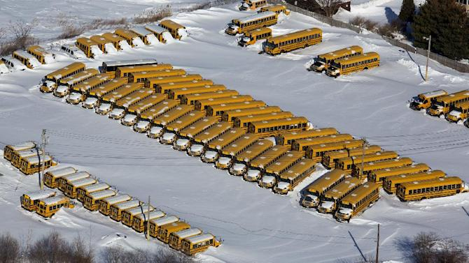 A row of school busses are buried in snow near Bridgeport, Conn., Sunday, Feb. 10, 2013, in the aftermath of a storm that hit Connecticut and much of the New England states. (AP Photo/Craig Ruttle)