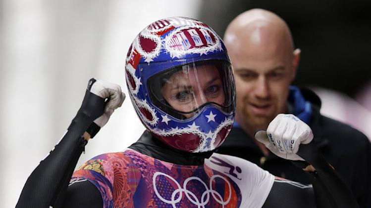 Noelle Pikus-Pace of the United States pumps her fists after her third run during the women's skeleton competition at the 2014 Winter Olympics, Friday, Feb. 14, 2014, in Krasnaya Polyana, Russia