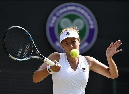 Irina-Camelia Begu of Romania hits a shot during her match against Maria Sharapova of Russia at the Wimbledon Tennis Championships in London