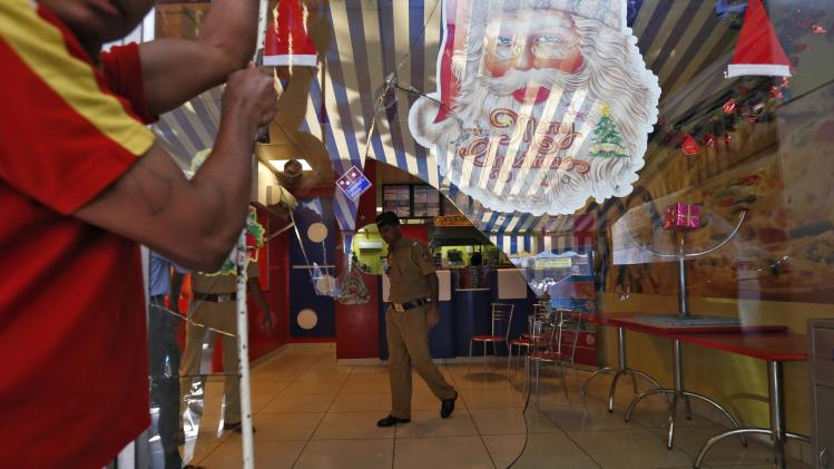 A policeman is seen through a broken glass window of a Dominos Pizza outlet after it was ransacked by activists in a Mumbai suburb