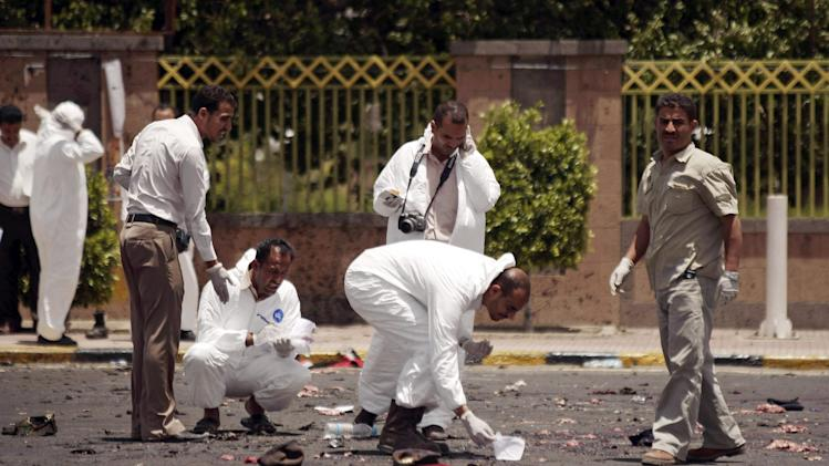 Forensic policemen collect evidence at the site of a suicide bomb attack at a parade square in Sanaa, Yemen, that killed at least 96 soldiers in one of the deadliest attacks in the city in years, Monday, May 21, 2012. The bombing appeared to be a failed assassination attempt against the Minister of Defense, Maj. Gen. Mohammed Nasser Ahmed, who arrived at the heavily secured city square to greet the assembled troops just minutes before the blast ripped through the area. (AP Photo/Hani Mohammed)
