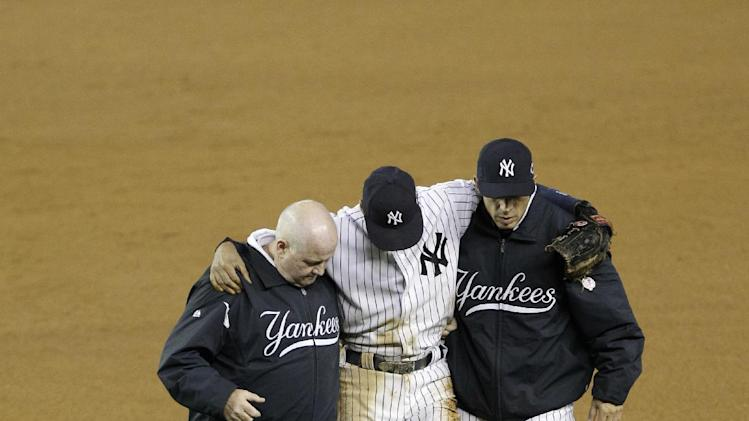 Trainer Steve Donohue, left, and New York Yankees manager Joe Girardi, right, help Derek Jeter off the field after he injured himself during Game 1 of the American League championship series against the Detroit Tigers Sunday, Oct. 14, 2012, in New York.  (AP Photo/Kathy Willens)