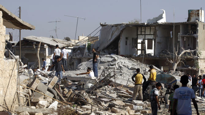 Syrians check the damage of destroyed houses after an air strike destroyed at least ten houses in the town of Azaz on the outskirts of Aleppo, Syria, Wednesday, Aug. 15, 2012. (AP Photo/ Khalil Hamra)