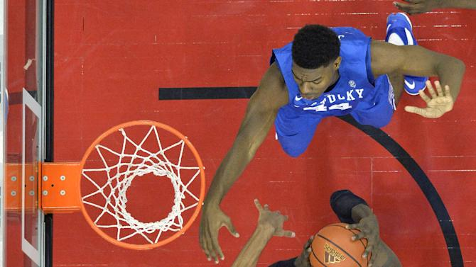 Louisville's Montrezl Harrell, center, attempts a shot through the defense of Kentucky's Dakari Johnson, top and Trey Lyles during the second half of an NCAA college basketball game Saturday Dec. 27, 2014, in Louisville, Ky. Kentucky won 58-50. (AP Photo/Timothy D. Easley)