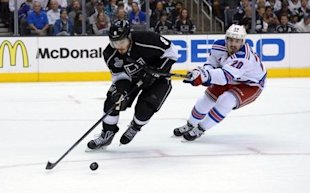 Doughty reaches for the puck against Rangers winger Chris Kreider during Game 1 of the 2014 Stanley Cup Final at Staples Ceneter in Los Angeles. (USA ...