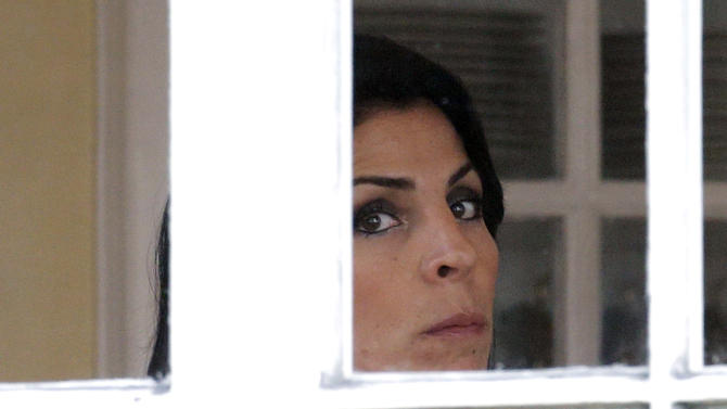 Jill Kelley looks out the window of her home Tuesday, Nov 13, 2012 in Tampa, Fla. Kelley is identified as the woman who allegedly received harassing emails from Paula Broadwell, paramour to Gen. David Petraeus. She serves as an unpaid social liaison to MacDill Air Force Base in Tampa, where the military's Central Command and Special Operations Command are located. (AP Photo/Chris O'Meara)