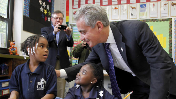 FILE - In this Oct. 27, 2011 file photo, Chicago Mayor Rahm Emanuel, right, visits with Brandy Toliver, left, and Mariah Neyland, in their first-grade class at the CICS Washington Park School on Chicago's South Side. The Chicago Public Schools extended the school day from 5 hours and 45 minutes to 7 hours in 2012 after a heated offensive by parents. Emanuel, a proponent of longer school days, had originally proposed a 7 1/2-hour school stay, but adjusted his proposal after discussions with parents, some of whom had been critical of the original plan. (AP Photo/Charles Rex Arbogast, File)