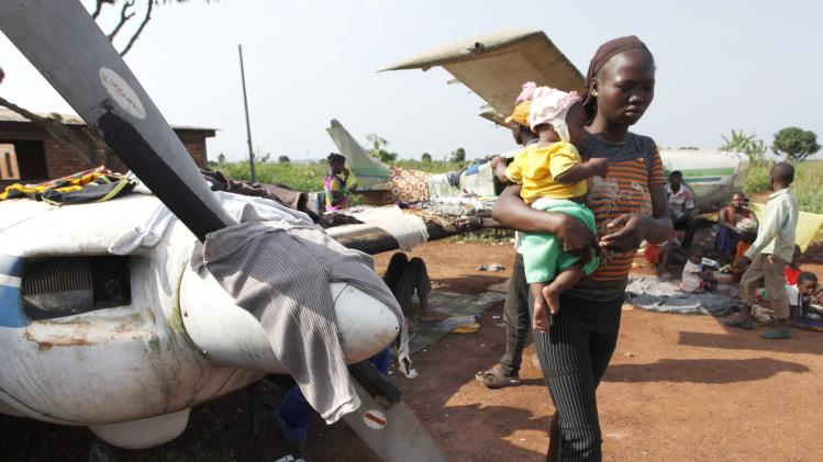 A woman walks while holding a baby at a camp in Bangui
