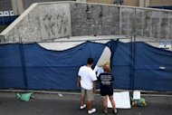"<p>Visitors look in on the site where the statue of former Penn State University football coach Joe Paterno once stood outside Beaver Stadium. The removal of the statue came on the same day that the National Collegiate Athletics Association, which governs major university sports programs, said it would announce ""corrective and punitive"" measures against Penn State on Monday.</p>"