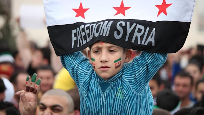 A Syrian boy waves the Syrian revolutionary flag during a celebration to commemorate the second anniversary of the Syrian revolution, in Amman, Jordan, Friday, March, 15, 2013. Around a thousand Syrians gathered in front of the Syrian embassy, and chanted slogans against Assad, and the Baath regime that has ruled Syria for the last 40 years. (AP Photo/Mohammad Hannon)