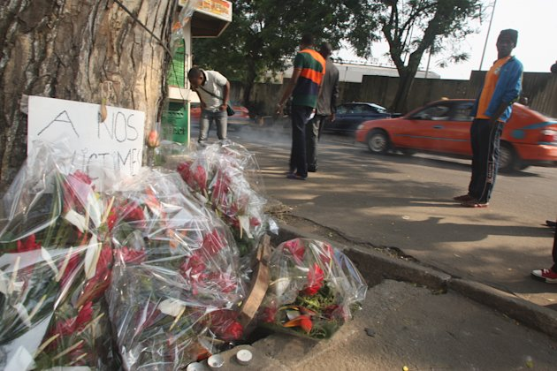 Flowers are left by a sign reading &quot;to our victims&quot; in Abidjan, Ivory Coast, Wednesday Jan. 2, 2013. Survivors of a stampede in Ivory Coast that killed 61 people, most of them children and teenagers, after a New Year&#39;s Eve fireworks display at a stadium said Wednesday that barricades stopped them from moving along a main boulevard, causing the crush of people. Ivory Coast President Alassane Ouattara ordered three days of national mourning and launched an investigation into to the causes of the tragedy but two survivors, in interviews with The Associated Press, indicated why so many died in what would normally be an open area, the Boulevard de la Republic. An estimated 50,000 people had gathered in Abidjan&#39;s Plateau district to watch the fireworks.(AP Photo/Emanuel Ekra)