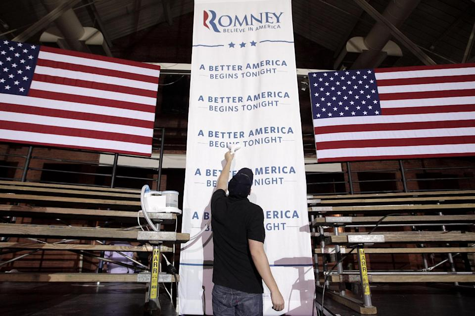 A worker irons a banner as he gets ready for an election night rally for Republican presidential candidate, former Massachusetts Gov. Mitt Romney, Tuesday, April 24,2012, in Manchester, N.H. (AP Photo/Jae C. Hong)