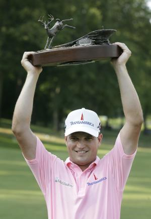 Zach Johnson holds the trophy after winning the John Deere Classic golf tournament at TPC Deere Run, Sunday, July 15, 2012, in Silvis, Ill.  Johnson defeated Troy Matteson in a playoff. (AP Photo/Charlie Neibergall)