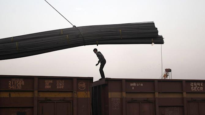 File photo shows a worker signalling to a crane operator unloading steel rods from a goods train at a railway yard in Ahmedabad