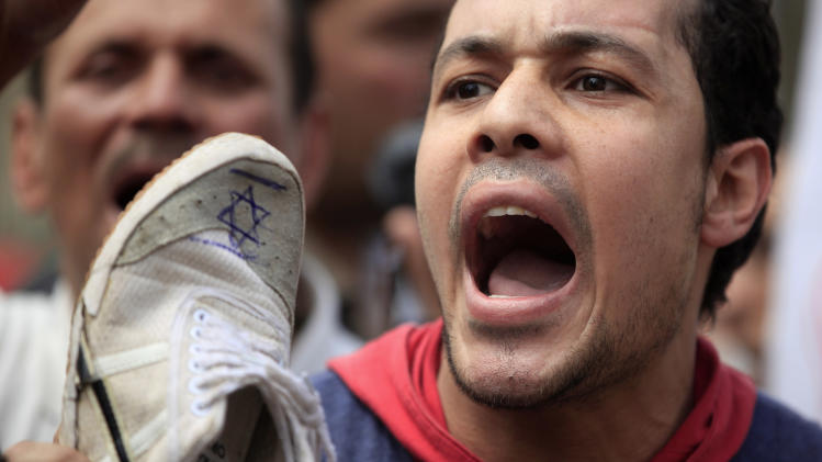 An Egyptian man chants slogans as he hold a shoe with an Israeli flag drawn on it during an anti-Israel protest held after the Friday noon prayer at Al-Azhar mosque in Cairo, Egypt, Friday, May 10, 2013. Egypt's Muslim Brotherhood staged an anti-Israel rally in Cairo on Friday, the first such protest by the main backers of President Mohammed Morsi since they rose to prominence in the wake of the country's 2011 uprising. (AP Photo/Khalil Hamra)