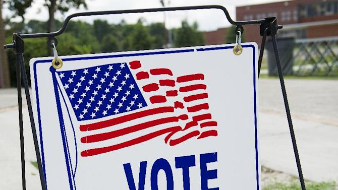"""FILE - In this July 22, 2014 file photo, A """"Vote Here"""" sign is seen outside the main entrance to the Fleming Park Bernie Ward Community Center during a run-off election day in Augusta, Georgia. (AP Photo/The Savannah Morning News, Sara Caldwell)"""