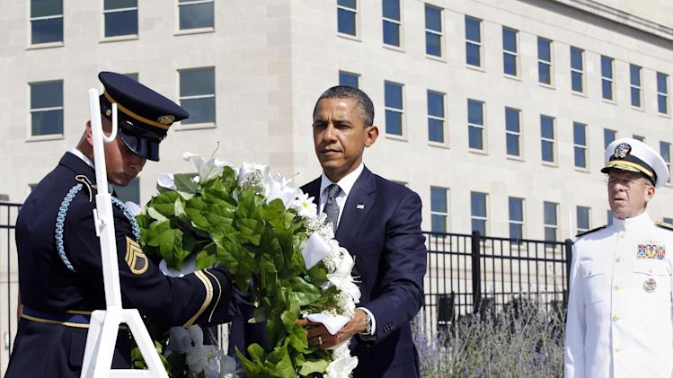 President Barack Obama lays a wreath as the 10th anniversary of the September 11 attacks are observed at the Pentagon in Washington, Sunday, Sept. 11, 2011. At right is Chairman of the Joint Chiefs of Staff Adm. Mike Mullen. (AP Photo/Charles Dharapak)