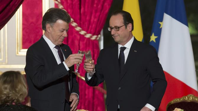 French President Francois Hollande toasts with Colombian President Juan Manuel Santos during an official dinner at the Elysee Palace in Paris