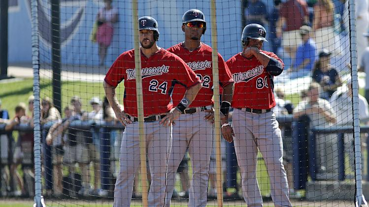 Minnesota Twins third baseman Trevor Plouffe (24), left fielder Wilkin Ramirez (22), and right fielder Jermaine Mitchell (80) stand behind a screen during batting practice before an exhibition baseball game against the Tampa Bay Rays in Port Charlotte, Fla., Tuesday, March 11, 2014. (AP Photo/Gerald Herbert)