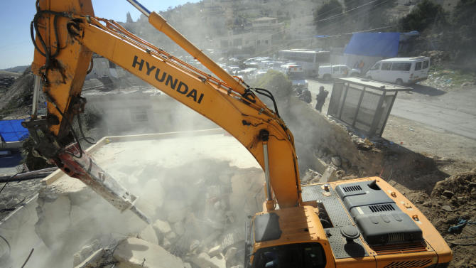 A bulldozer works on a Palestinian home demolished in East Jerusalem Wednesday, Feb. 5, 2014, Three Palestinian homes were demolished in the neighborhood, as the Israeli planners Wednesday gave final approval for 558 apartments in Jewish settlements in war-won east Jerusalem. (AP Photo/Mahmoud Illean)