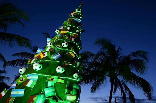 A Christmas tree with football-themed decorations and flags is seen as the sun goes down on the eve of the Brazil 2014 FIFA Football World Cup final draw, in Costa do Sauipe, Bahia state, on December
